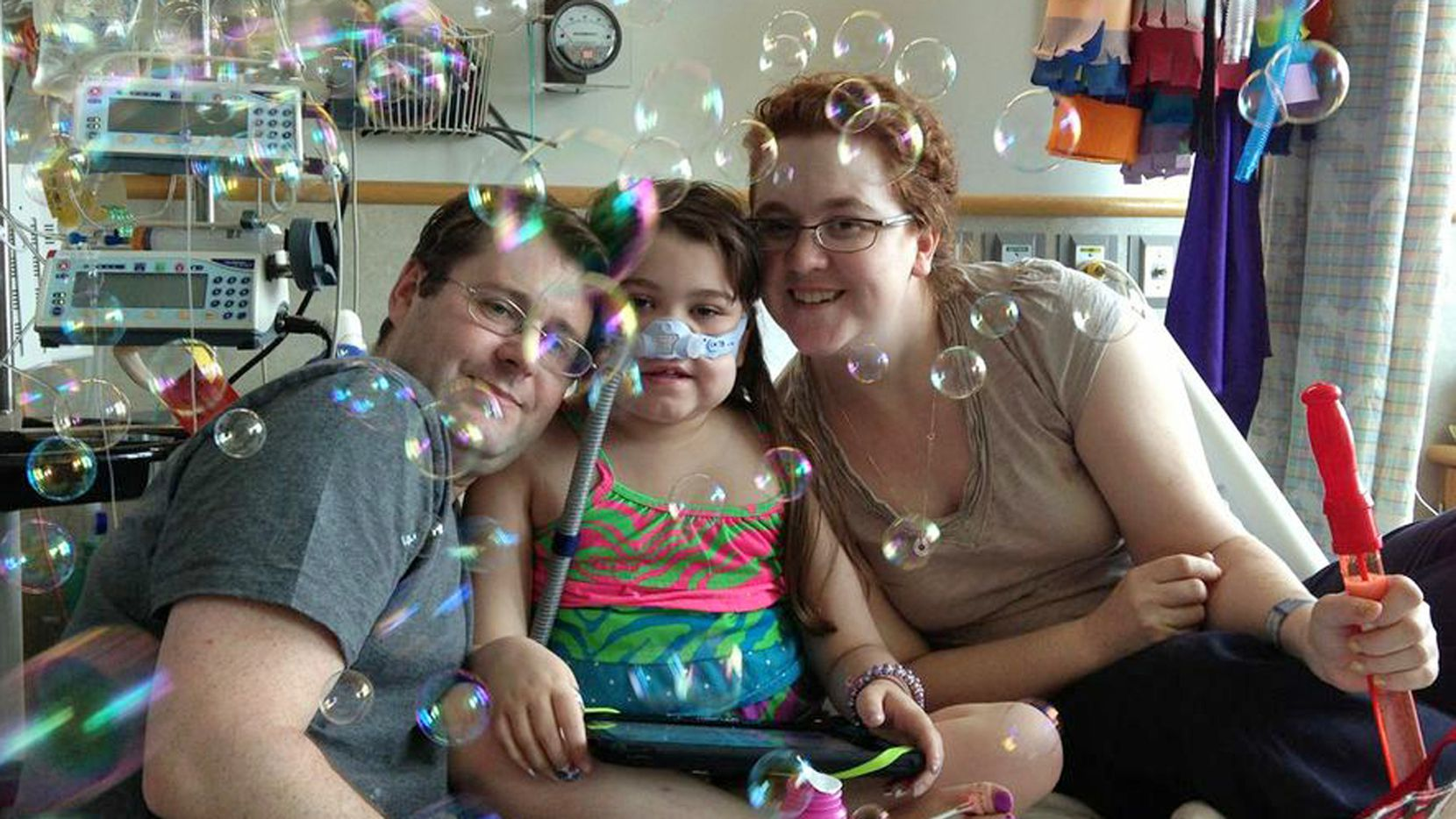 In this May 30, 2013 file photo provided by the Murnaghan family, Sarah Murnaghan, center, celebrates the 100th day of her stay in Children's Hospital of Philadelphia with her father, Fran, left, and mother, Janet. The 10-year-old suburban Philadelphia girl received a lung transplant there June 12, 2013, her family said. (AP Photo/Murnaghan Family, File)