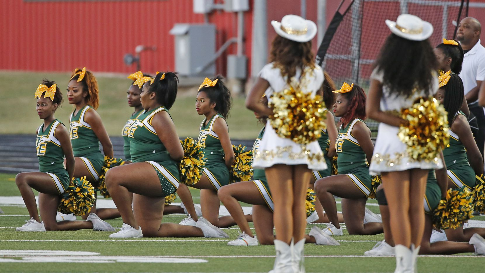 DeSoto cheerleaders take a knee during the playing of the national anthem before the DeSoto High School Eagles vs. the Cedar Hill High School Longhorns high school football game in Cedar Hill, Texas on Friday, September 23, 2016. The teams were not on the field at the time the anthem was played.