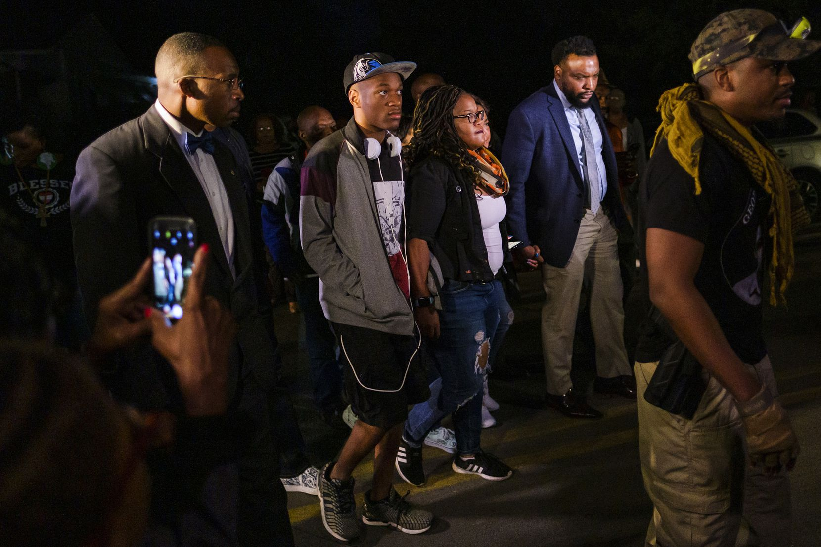 Attorney Lee Merritt (right) walks with members of the victimÕs family as they arrive at community vigil for Atatiana Jefferson on Sunday, Oct. 13, 2019, in Fort Worth.