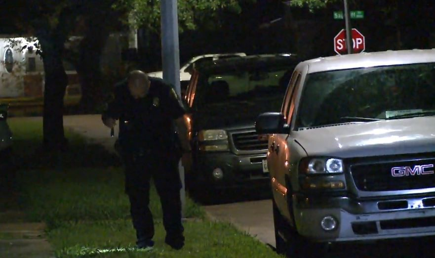 A Houston police officer looks for evidence after a home invasion Friday morning in the southeastern part of the city.
