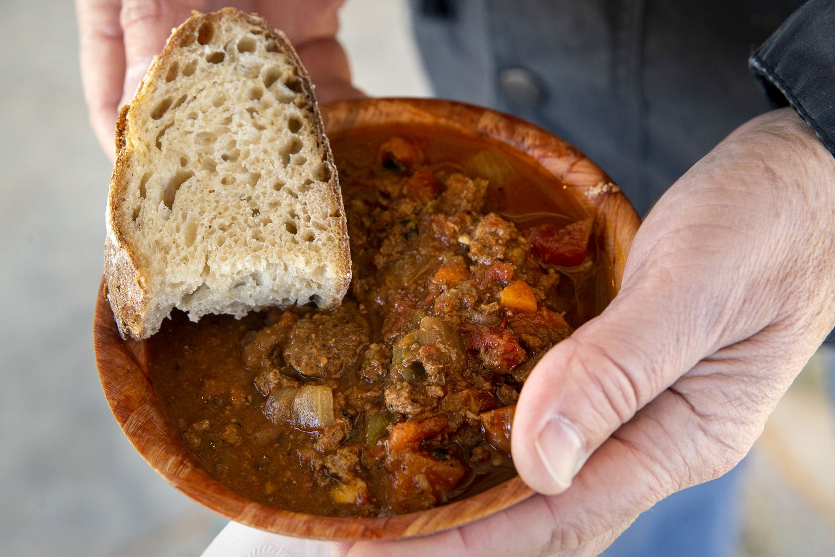 A man holds locally sourced bison chili provided to paying attendees of a bison field harvest event at Roam Ranch in Fredericksburg.