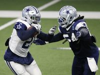 Dallas Cowboys running back Ezekiel Elliott (21) is tackled by Dallas Cowboys linebacker Jaylon Smith (54) during training camp at the Dallas Cowboys headquarters at The Star in Frisco, Texas on Thursday, August 27, 2020.