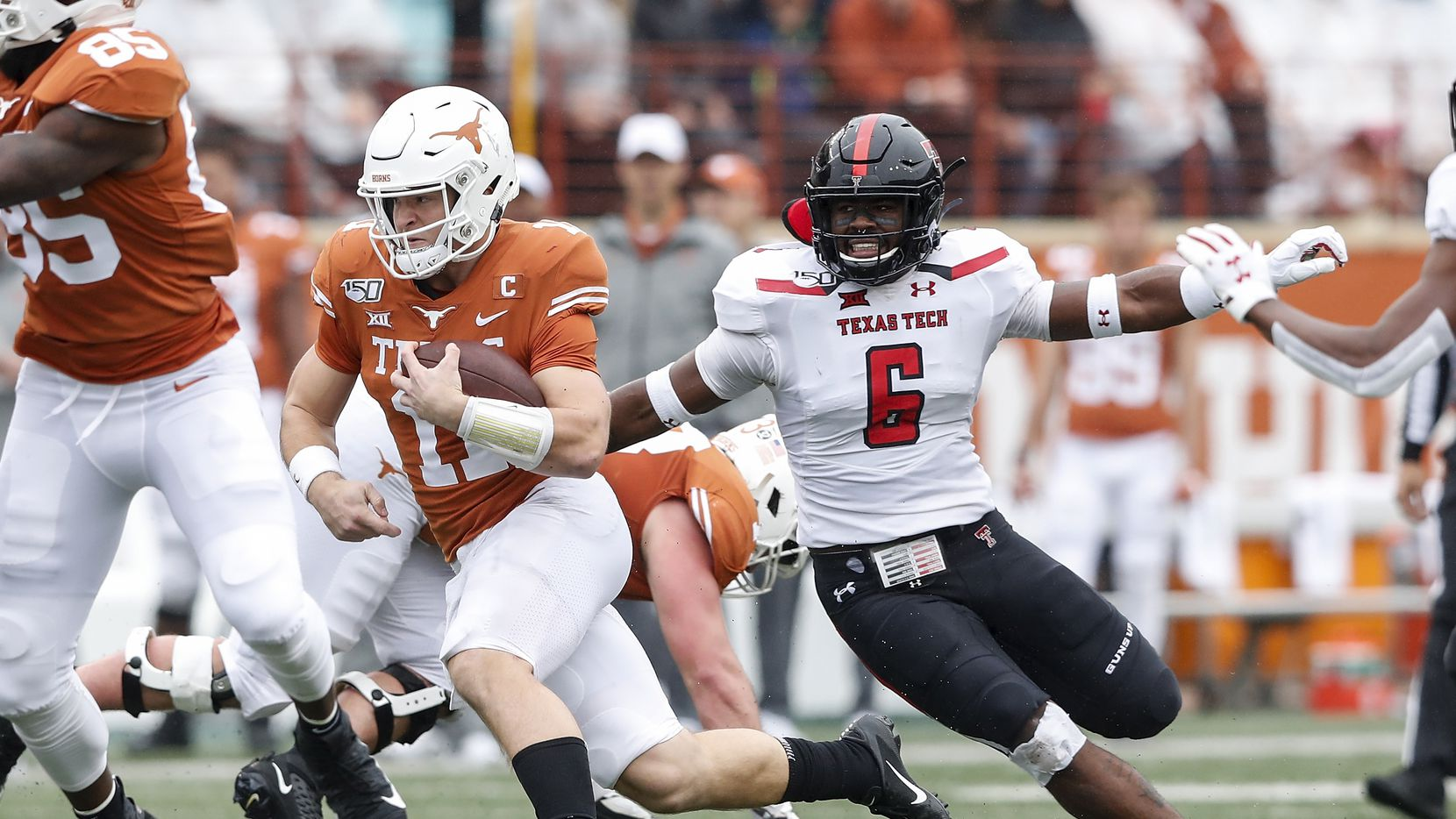 AUSTIN, TX - NOVEMBER 29:  Sam Ehlinger #11 of the Texas Longhorns runs the ball defended by Riko Jeffers #6 of the Texas Tech Red Raiders in the first quarter at Darrell K Royal-Texas Memorial Stadium on November 29, 2019 in Austin, Texas.