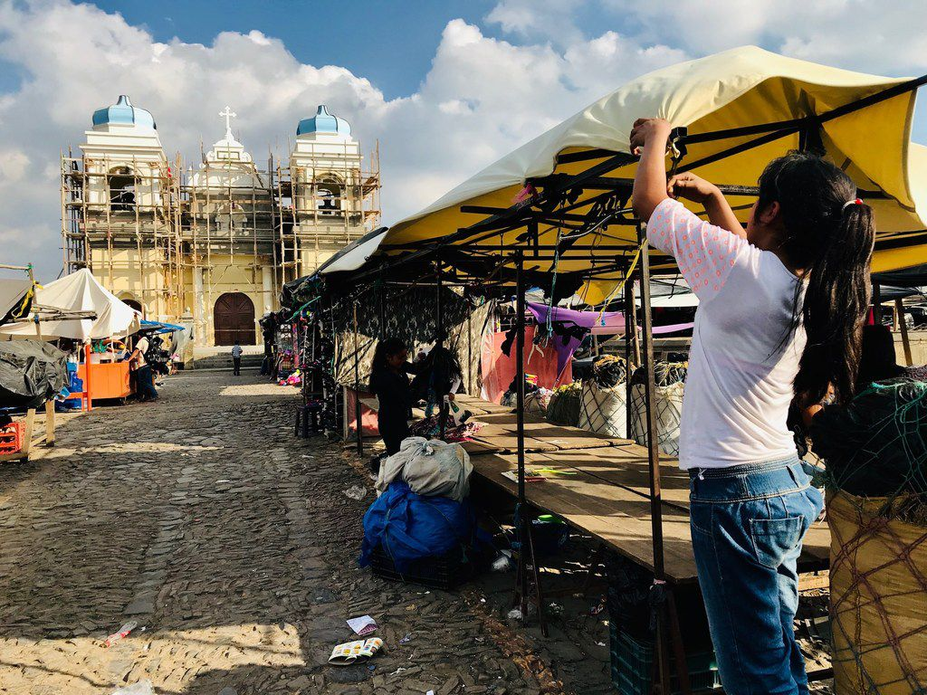 Workers at the open-air market in San Martin Jilotepeque pack up to leave. The church is undergoing renovation with help from remittances sent from abroad, including families in Texas.
