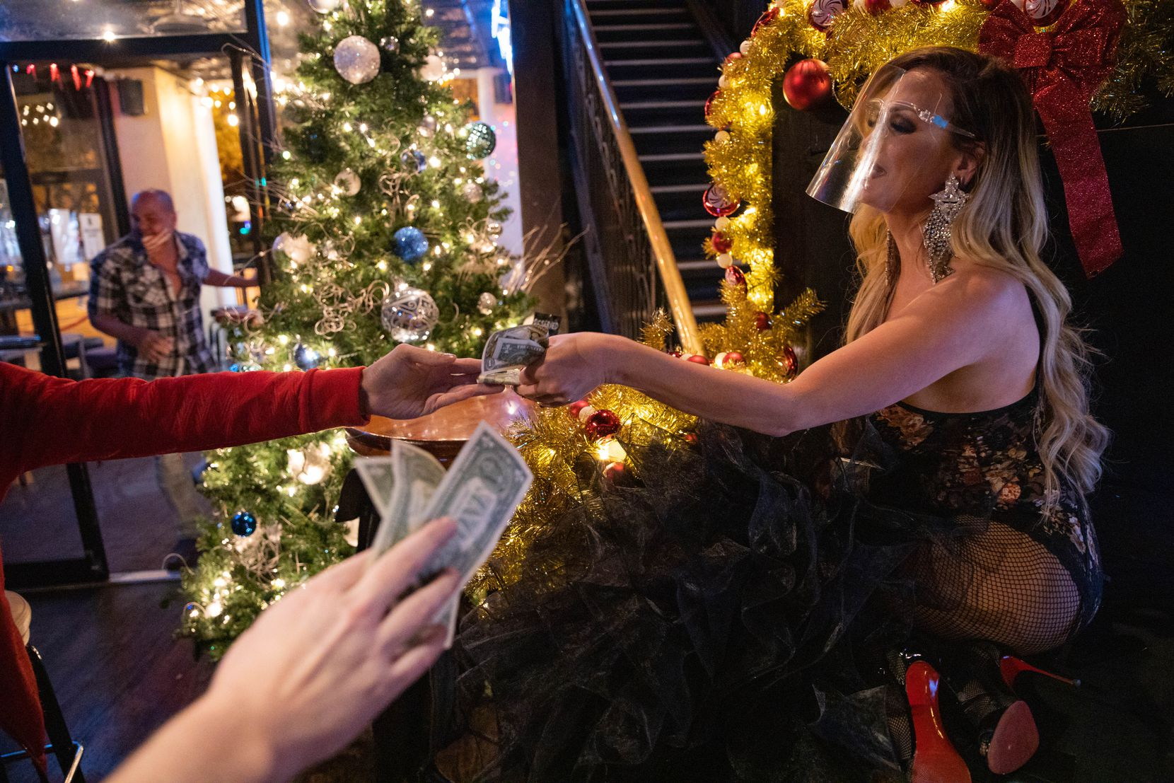Krystal Summers accepts tips while performing Dec. 12 at JR's Bar and Grill in Dallas during the first drag show since pandemic restrictions began.