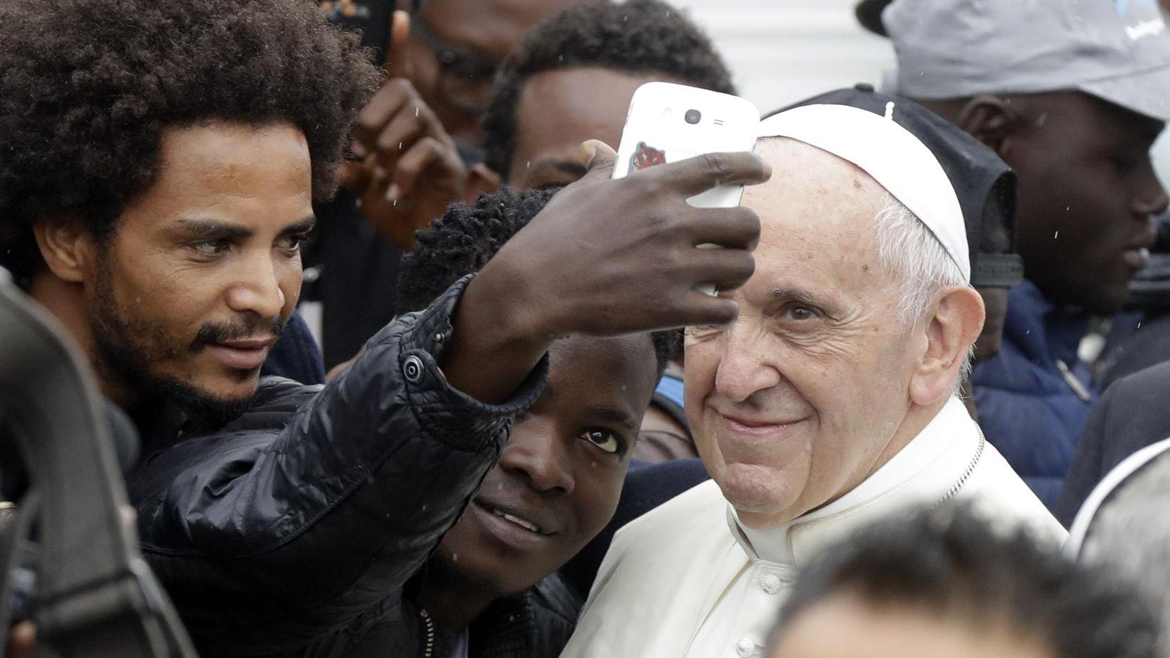 El Papa Francisco posa para tomarse una fotografía junto a un inmigrante de Africa en Bologna, Italia.(AP)