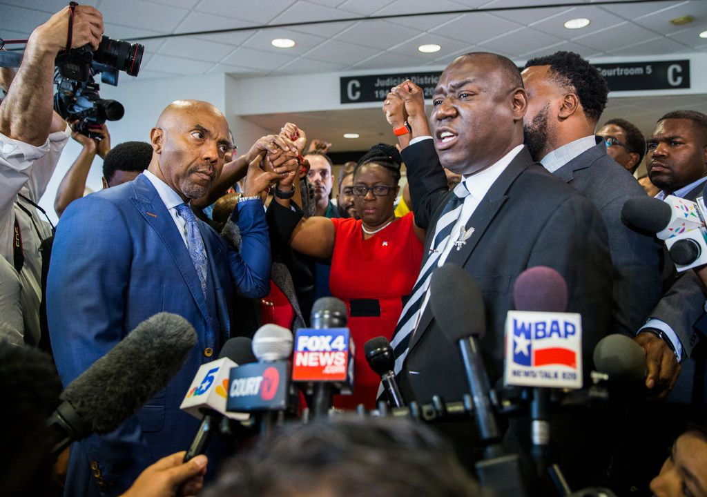 Attorneys Daryl K. Washington (left) and Ben Crump raise the hands of Botham Jean's mother, Allison Jean (center), after Tuesday's guilty verdict in the trial of Amber Guyger.