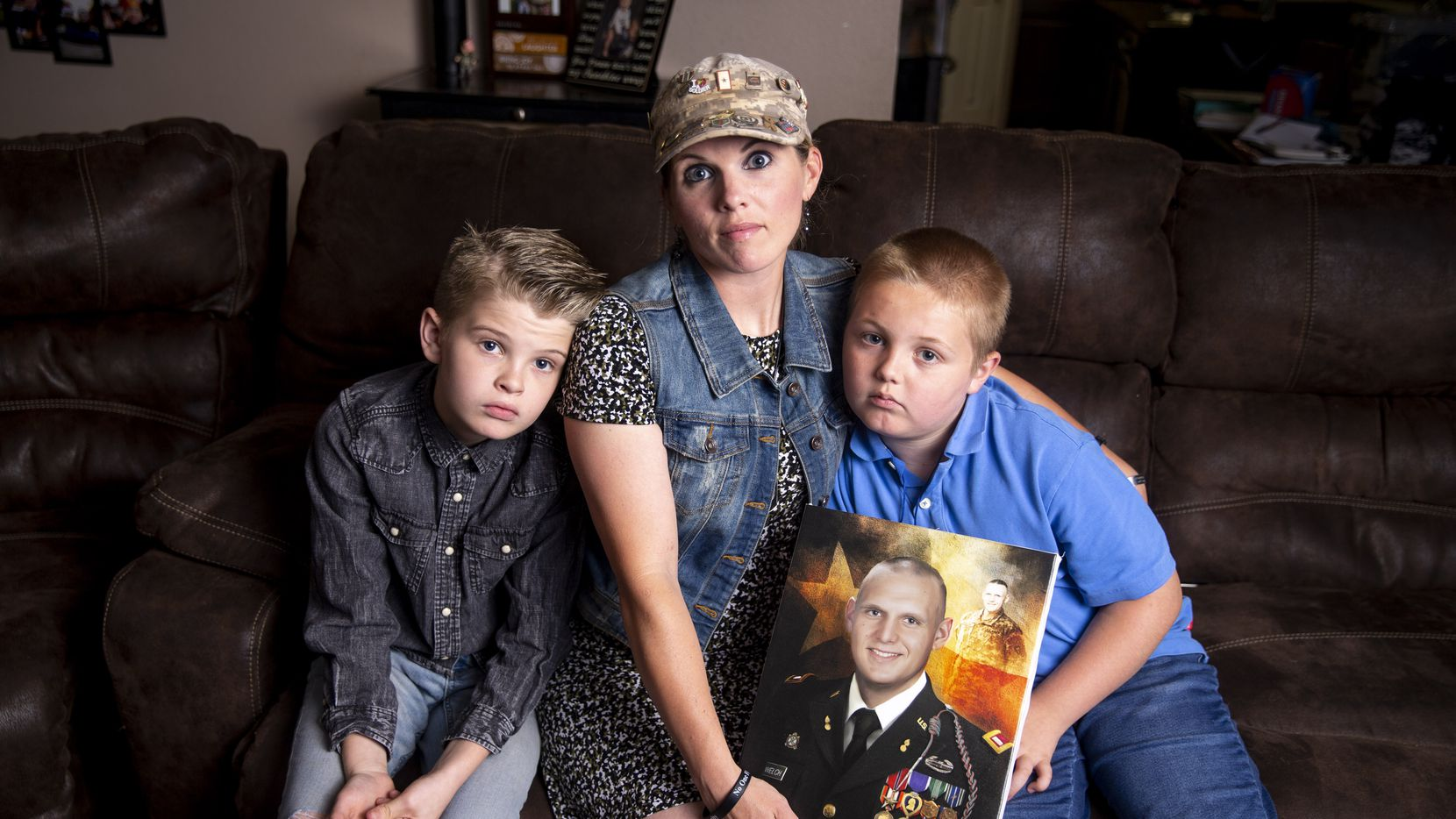 Becky Welch poses with her sons Aaden Welch, 11, left, and Robby Welch, 9, with a portrait of Army 1st Lt. Robert Welch, in their Wylie, Texas home Friday, May 31, 2019. A provision in the 2017 tax overhaul caused the Welch family's tax bill to increase.