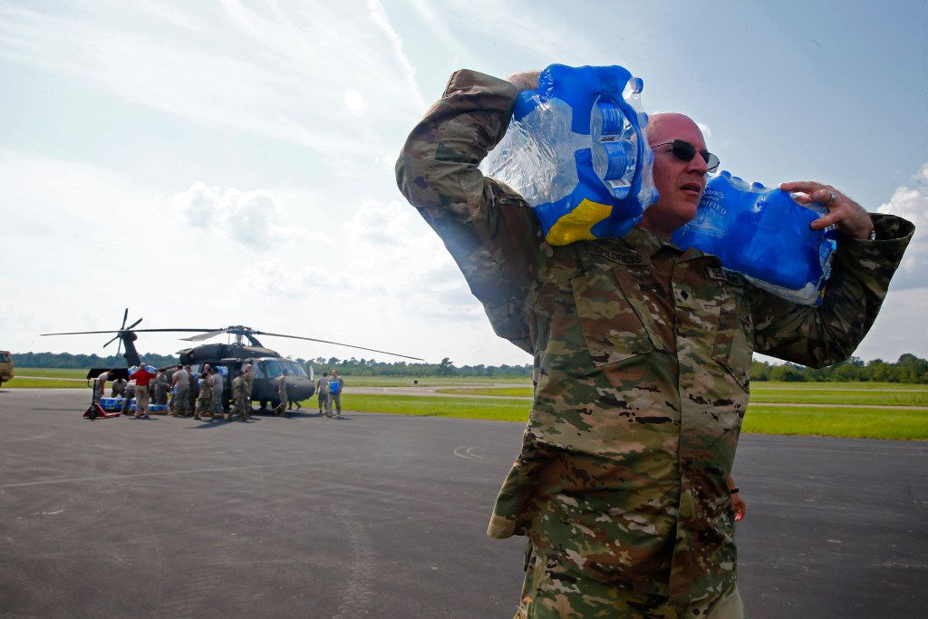Sgt. Kevin Childress unloads water with the Texas National Guard (4th Battalion, 133rd Regiment) after Hurricane Harvey at the Orange County Airport in Orange, Texas, on Sunday.