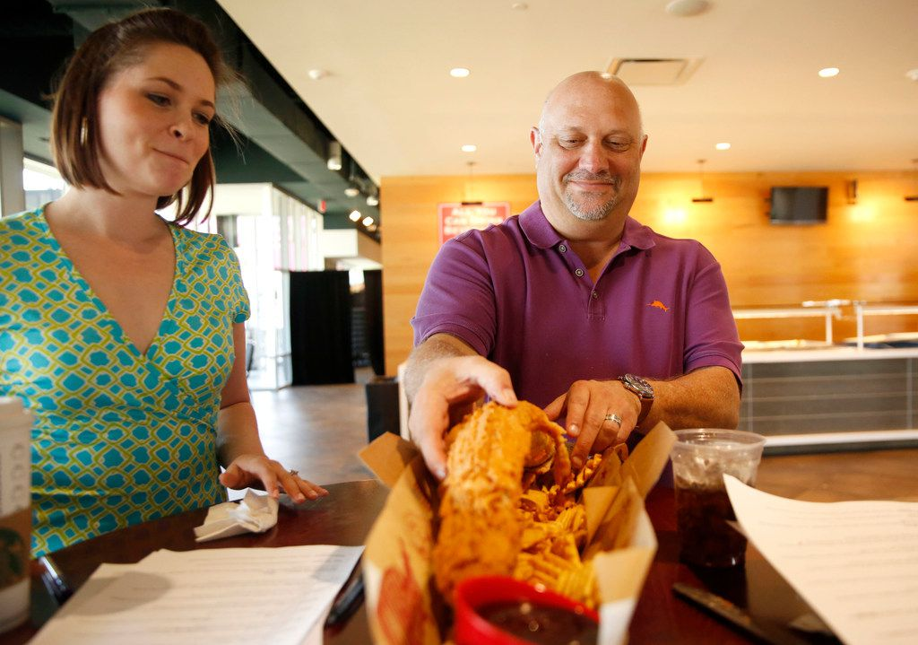Dallas Morning News Texas Rangers writer Evan Grant tries the new Fowl Pole, a two-pound chicken tender, alongside GuideLive writer Sarah Blaskovich at Globe Life Park in Arlington Texas on Monday, March 25, 2019. (Rose Baca/Staff Photographer)