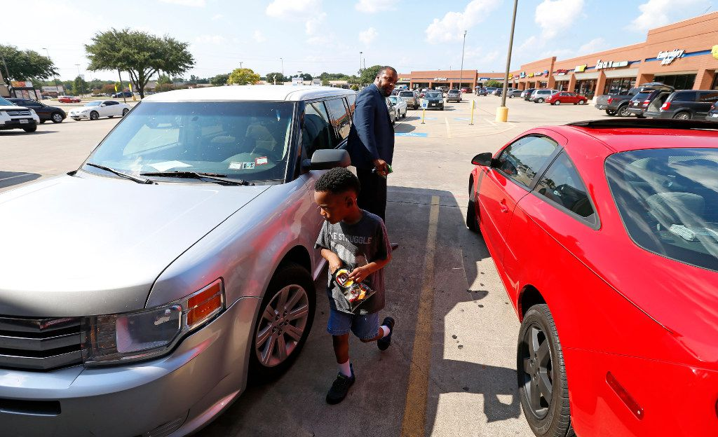Attorney Lee Merritt (top) opens a door for his 7-year-old son Stacy Merritt, Jr., after they have snacks and sandwiches at a Subway store in Allen.