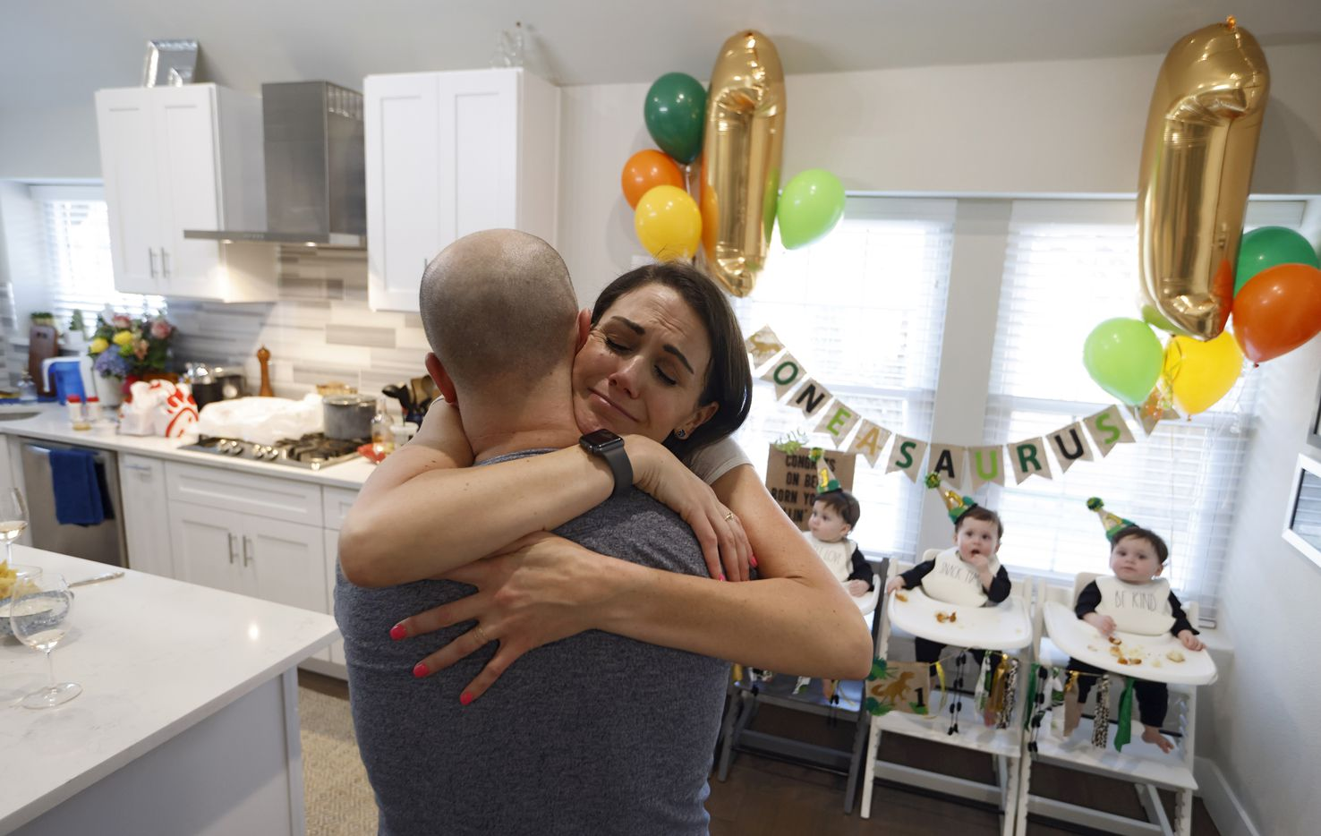 Jenny and Chris Marr hug each other as their sons, Harrison, Hardy, Henry, Hudson Marr eat dinner during their one year birthday party at their home on Monday, March 15, 2021in Grapevine, Texas.