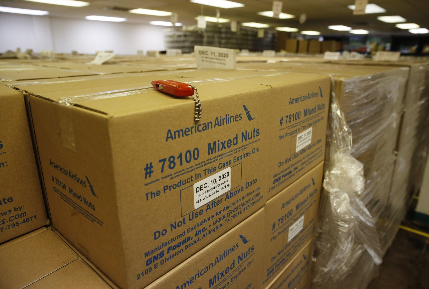 Boxes of mixed nuts sit at GNS Foods in Arlington. GNS last year sold airlines 12 million pounds of nuts that were dished out warm as a premium service to first-class customers. Sales to airlines have plunged because of the COVID-19 pandemic.