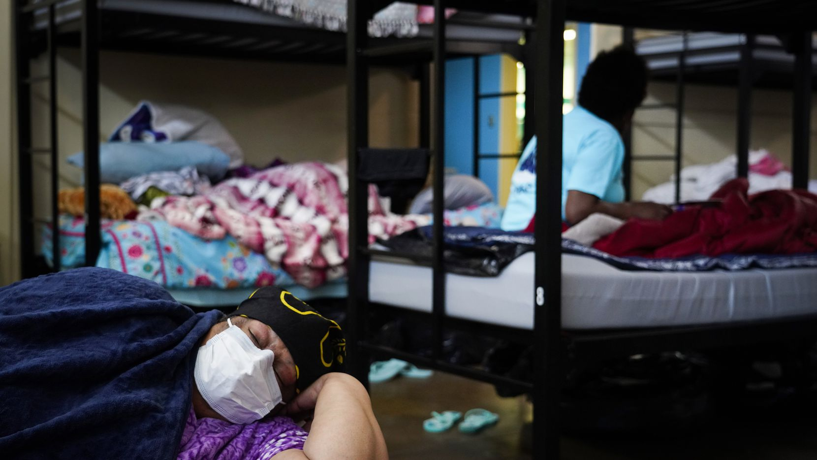 L. A. White wears a face mask as she rests in a bunk at Austin Street Center on Wednesday, March 11, 2020, in Dallas. White said she suffers from COPD (chronic obstructive pulmonary disease) among other respiratory conditions. The homeless shelter is adjusting to try to prevent the spread of the new coronavirus to one of the most vulnerable populations in the city. Clients at high risk, or sick clients, are also provided with masks. Shelter officials said they are distributing masks sparingly to preserve supply.