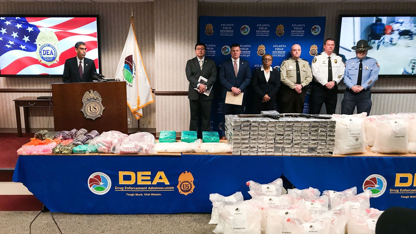 U.S. Drug Enforcement Administration Acting Administrator Uttam Dhillon announces the launch of Operation Crystal Shield at a news conference in Atlanta on Thursday, Feb. 20, 2020. On the tables and floor in front of him are evidence bags containing about 1,300 pounds of processed crystal meth seized in suburban Atlanta, along with about 100 gallons of a product that could be cooked into about 5 to 7 pounds of crystal meth per gallon. The drugs shown here represent about 2.3 million individual doses, the DEA said.