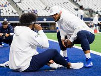 FILE - Cowboys quarterback Dak Prescott (4) talks with running back Ezekiel Elliott (21) as they warm up before a game against the New York Giants on Sunday, Sept. 8, 2019, at AT&T Stadium in Arlington.