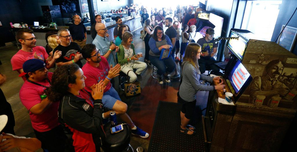 Fans cheer as Lauren Featherstone marks the 24th hour of playing tapper to break the world record for the classic arcade game at Free Play in Arlington on July 14.