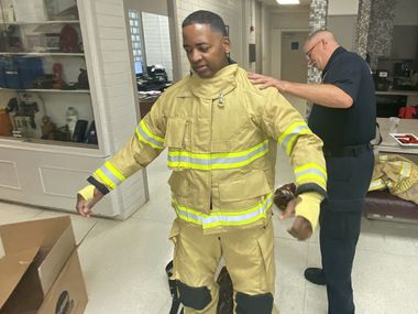 A Mesquite firefighter is fitted with new bunker gear. The city's fire department now has two sets of gear per firefighter, allowing one to be cleaned of possible carcinogens while the other is in use.