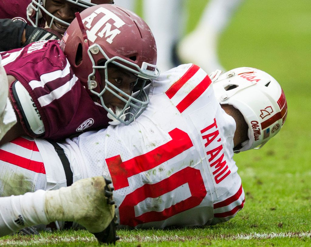 Texas A&M Aggies defensive lineman Justin Madubuike (52) lands on top of Ole Miss Landsharks quarterback Jordan Ta'amu (10) during a sack during the fourth quarter of a college football game between Texas A&M and Ole Miss on Saturday, November 9, 2018 at Kyle Field in College Station, Texas. (Ashley Landis/The Dallas Morning News)