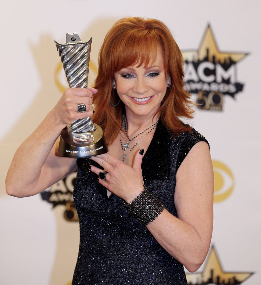 Reba McEntire poses for a photo with her Milestone Award during the 2015 Academy of Country Music Awards Sunday, April 19, 2015 at AT&T Stadium in Arlington, Texas.