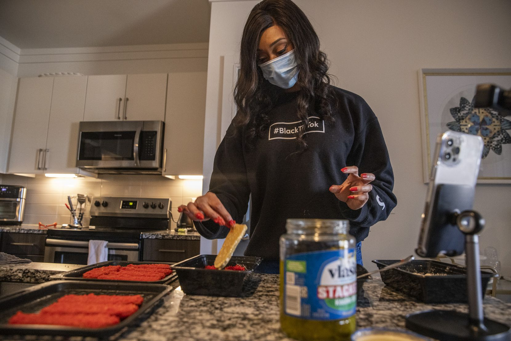 NaTasha Peck, creator of the YouTube channel ToshPointFro, creates Hot Cheetos fried pickle slices at her home in Frisco.