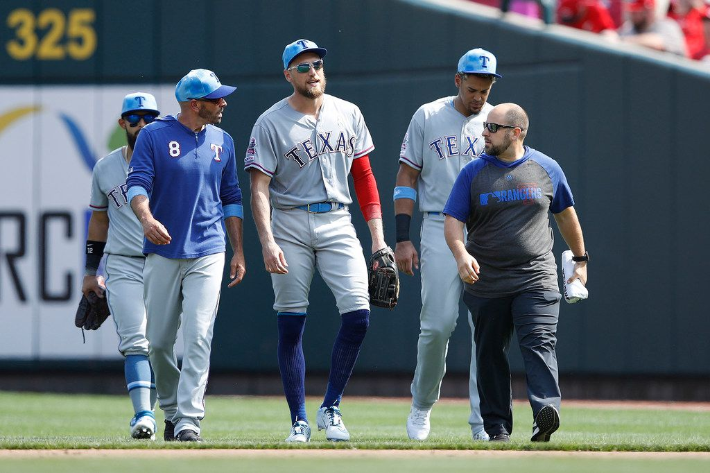 Hunter Pence (24) of the Texas Rangers walks off the field with manager Chris Woodward after suffering an injury in the fifth inning against the Cincinnati Reds on Sunday, June 16, 2019 at Great American Ball Park in Cincinnati, Ohio. (Joe Robbins/Getty Images/TNS)
