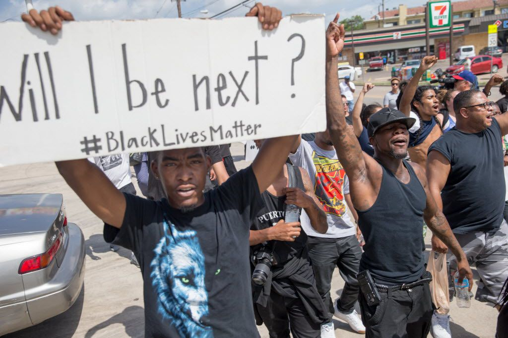 Niamke Ledbetter, 21, of Oakcliff, Dallas, marches with signs along with other Black Lives Matter on Park Ln on July 10, 2016 in Dallas. (Ting Shen/The Dallas Morning News)