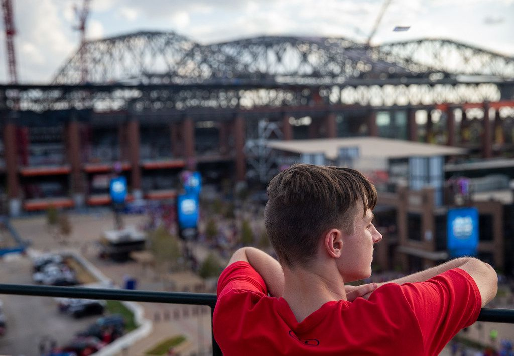 Connor Dill, 16 and from Arlington, looks out at the new Globe Life Field from the top level of Globe Life Park following the Texas Rangers' final season game in Arlington, Texas, on Sunday, Sep. 29, 2019. Following the game, fans enjoyed a ceremony and parade to place home plate at the adjacent Globe Life Field.