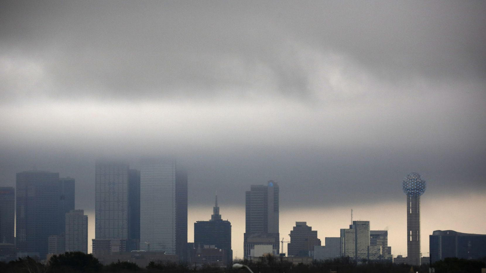 Low clouds developing along the cold front pass through buildings in downtown Dallas, Tuesday morning, February 4, 2020. Temperatures are expected to drop throughout the day ahead of some wintry precipitation overnight. (Tom Fox/The Dallas Morning News)