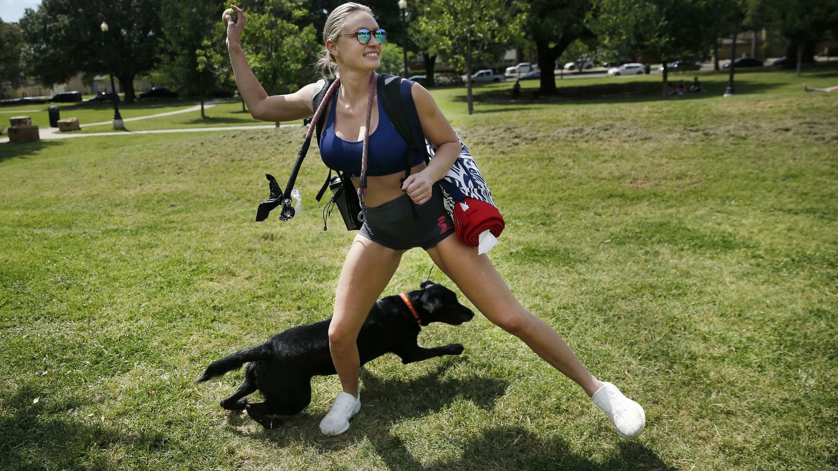 Amanda Calhoun of Dallas throws a tennis ball to her black lab KC at Cole Park on Friday.  She says she took the rest of Friday off to come to the park and relax. (