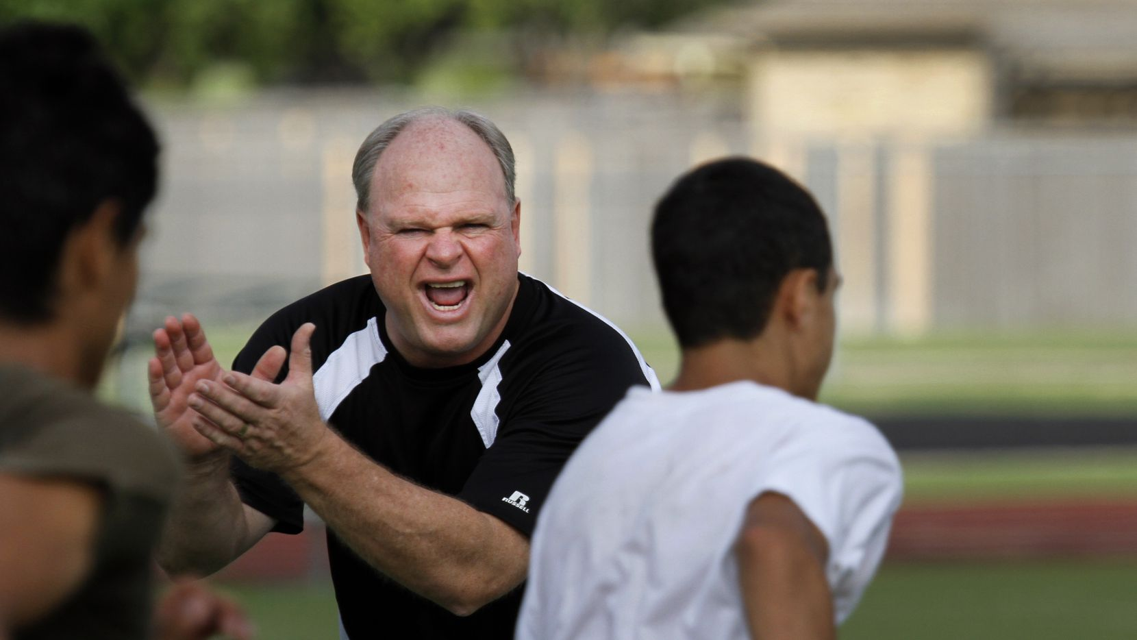 Jim Ledford, head football coach and athletic coordinator at Berkner High School, cheers up students during a running session of their strengthening & conditioning camp on July 14, 2010.