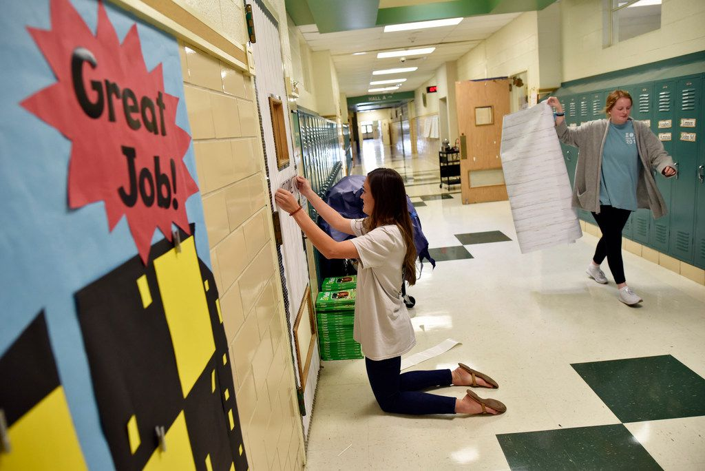 First-grade teachers Natalie Ryan (left) and Hannah Hogg prepare their classroom doors for the first day of school at Terrance Elementary on Thursday in Richardson.