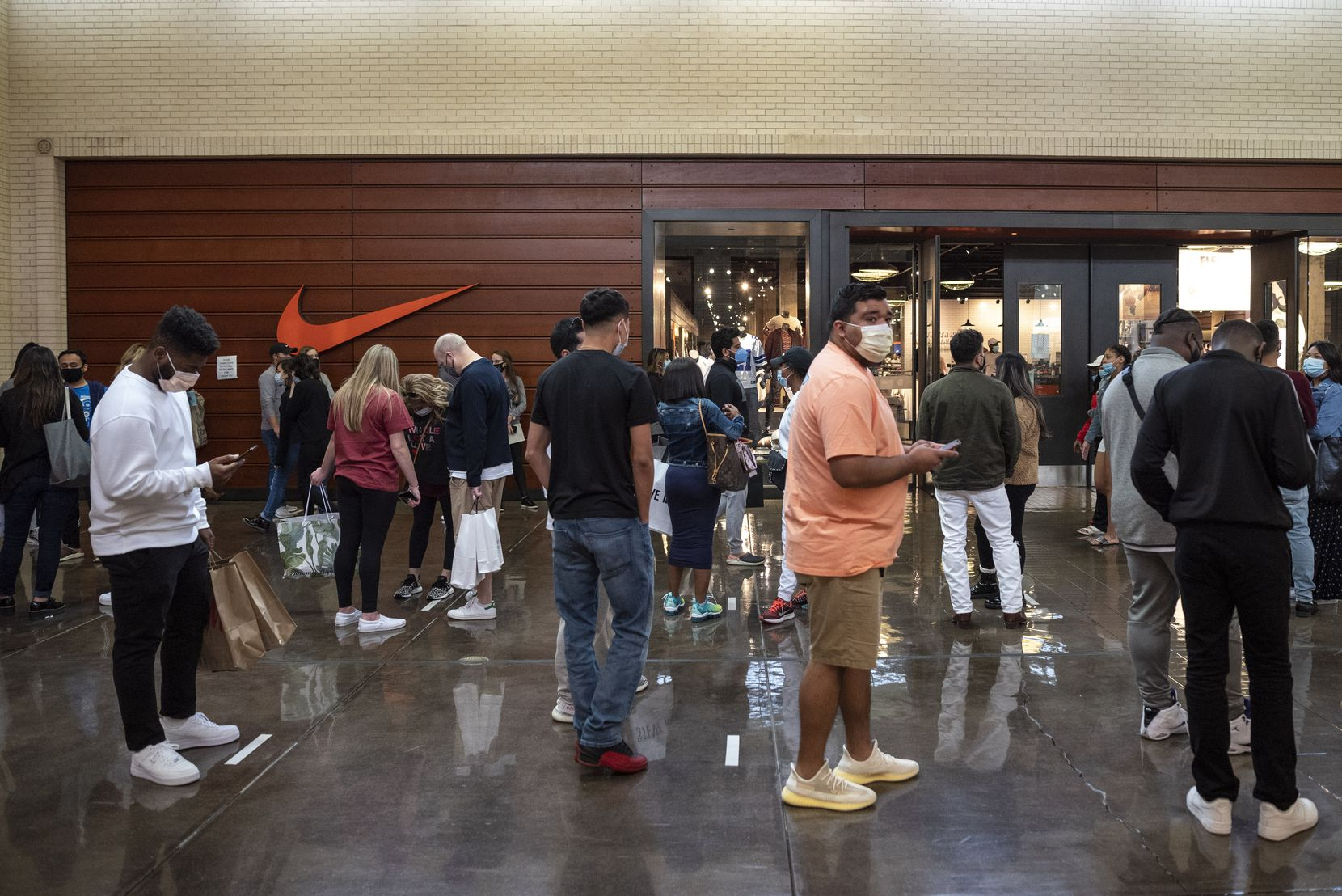A long line of shoppers snakes in front of the Nike store during Black Friday at NorthPark Center in Dallas.