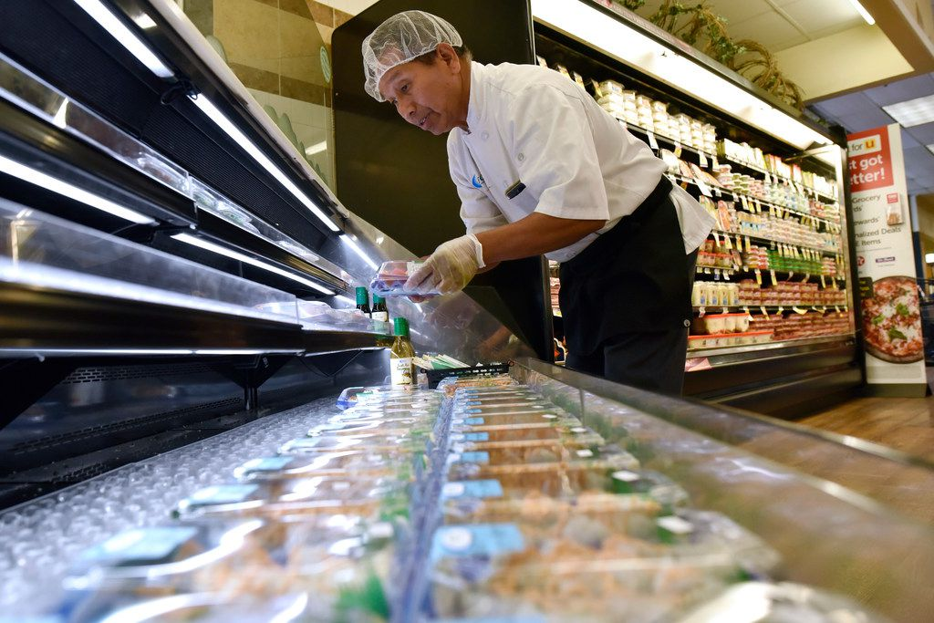 Sushi chef Simon Cham stocks fresh sushi rolls at the sushi station inside the Albertsons at the Casa Linda shopping center in Dallas.