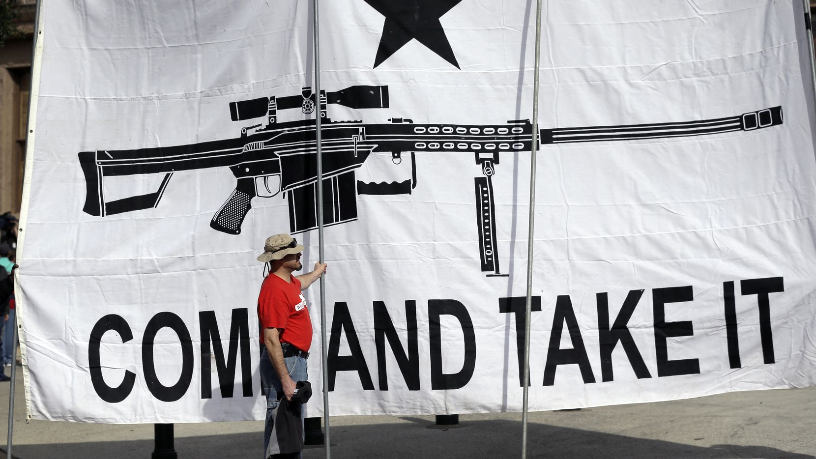 "A demonstrator helps hold a large ""Come and Take It"" banner at a rally in support of open carry gun laws at the Capitol in Austin in January."