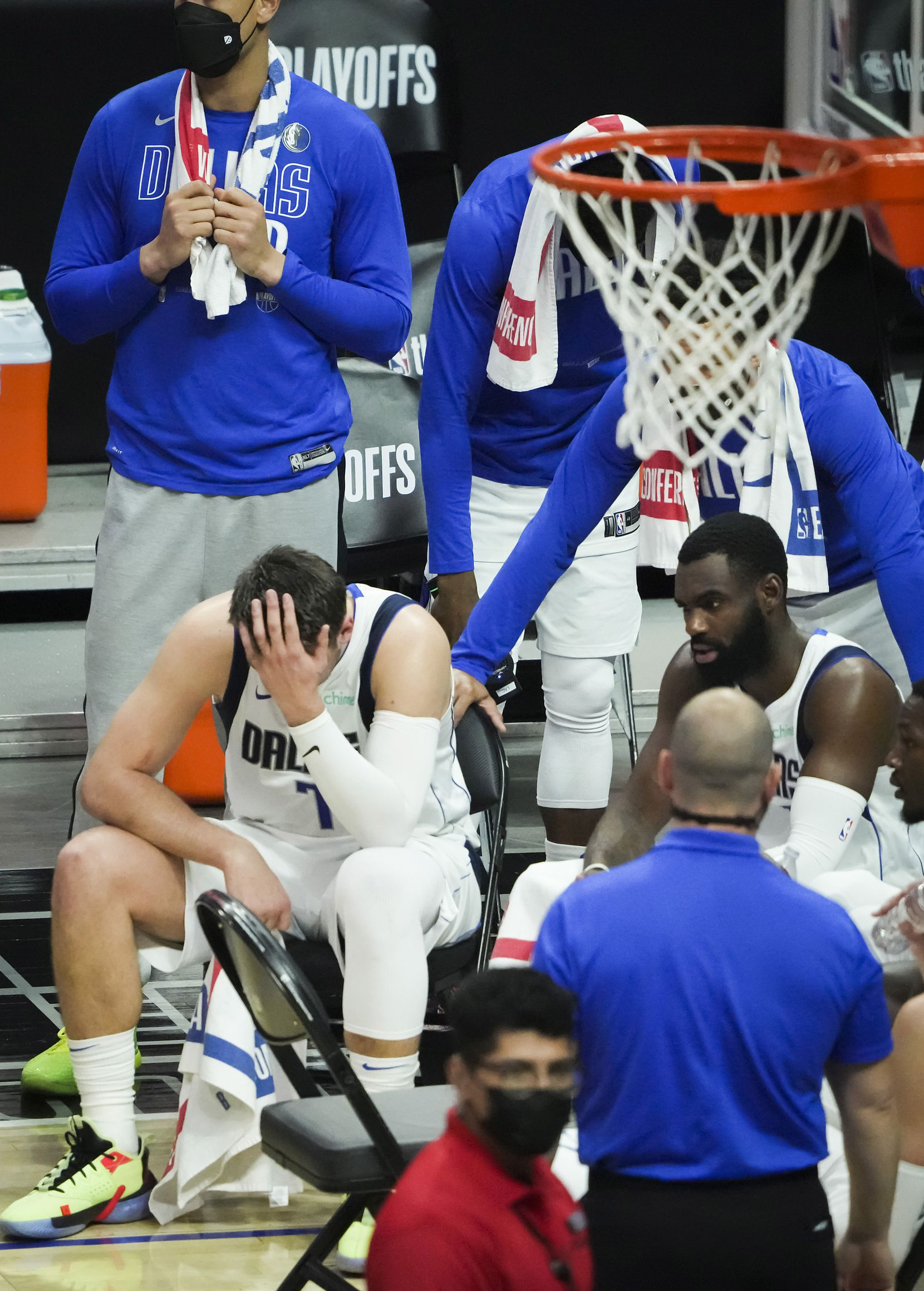 Dallas Mavericks guard Luka Doncic (bottom left)  hangs his head during a timeout with forward Tim Hardaway Jr. (right) in the fourth quarter of a loss to the LA Clippers in Game 7 of an NBA playoff series at the Staples Center on Sunday, June 6, 2021, in Los Angeles.