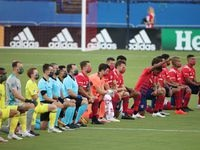 FRISCO, TX - AUGUST 12: Players of FC Dallas and Nashville SC  get to their knees during the national anthem at Toyota Stadium in Frisco, Texas. (Photo by Omar Vega / Al Dia)