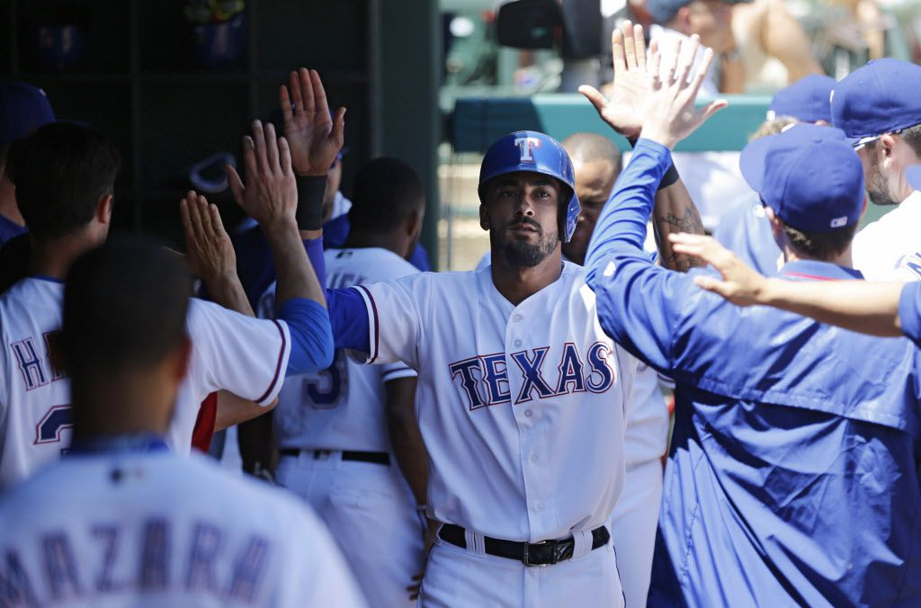 Texas Rangers outfielder Ian Desmond (20) is congratulated by teammates after scoring a run off a single from Delino DeShields (3) in a game against the Los Angeles Angels during the fourth inning of play at Globe Life Park in Arlington, on Sunday, May 1, 2016.  (Vernon Bryant/The Dallas Morning News)