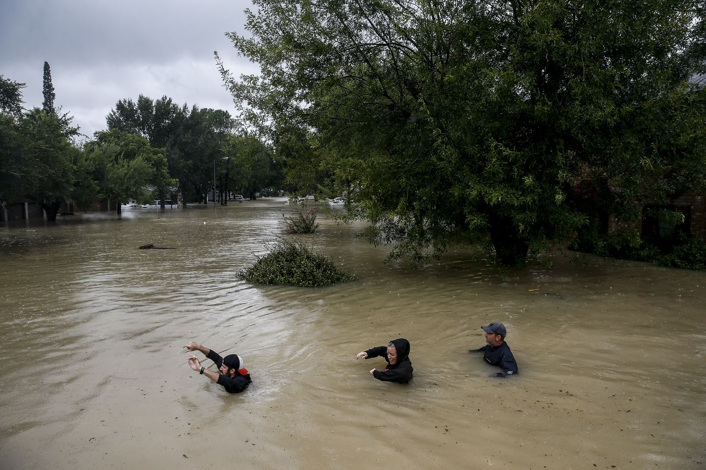 People wade through chest deep water down Pine Cliff Drive as Addicks Reservoir nears capacity due to near constant rain from Tropical Storm Harvey, Tuesday, Aug. 29, 2017 in Houston.