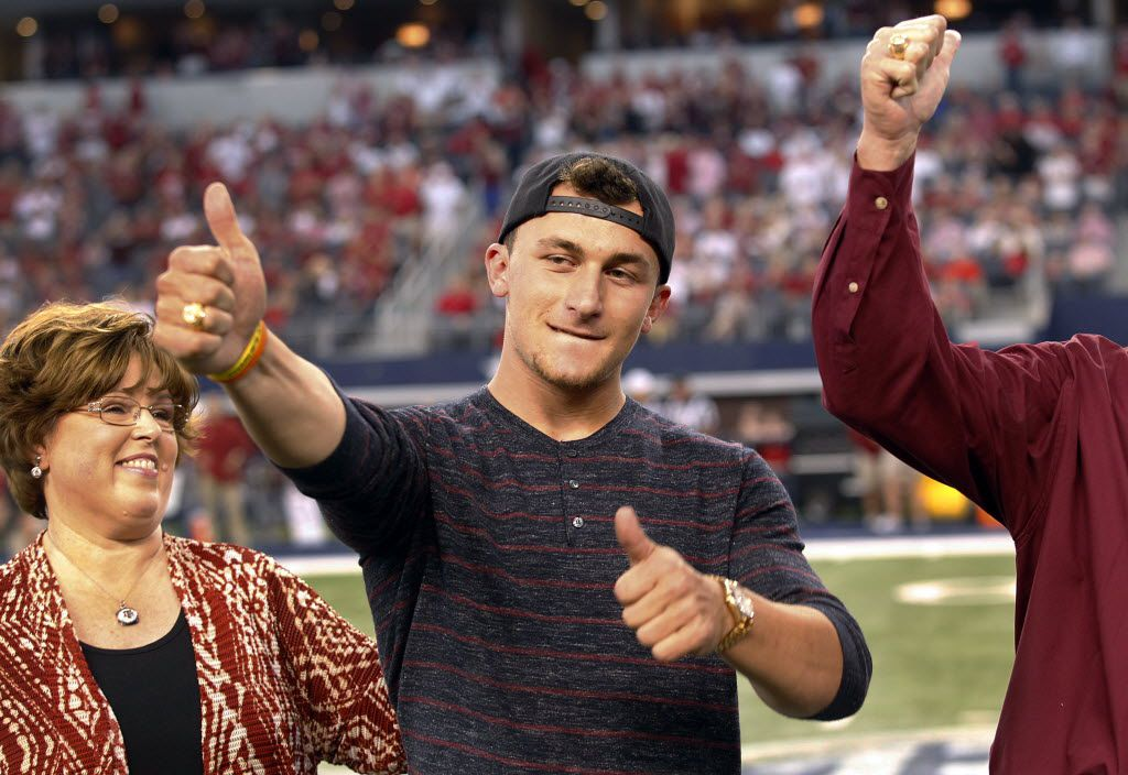 Former Texas A&M Aggies quarterback Johnny Manziel receives his Aggie Ring from his academic advisor Lee Hood, left, and Portner Garner III, president and CEO of the Association of Former Students during halftime  of the Southwest Classic football game between the Arkansas Razorbacks and Texas A&M Aggies at AT&T Stadium in Arlington, Texas, Saturday, September 27, 2014.  (Tom Fox/The Dallas Morning News)