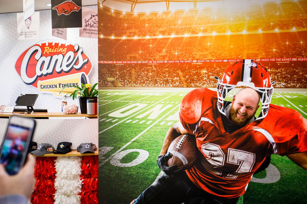 Employee Andrew Ross poses for a photo in a football display that fills the lobby at the Raising Cane's Dallas Restaurant Support Office in Plano.