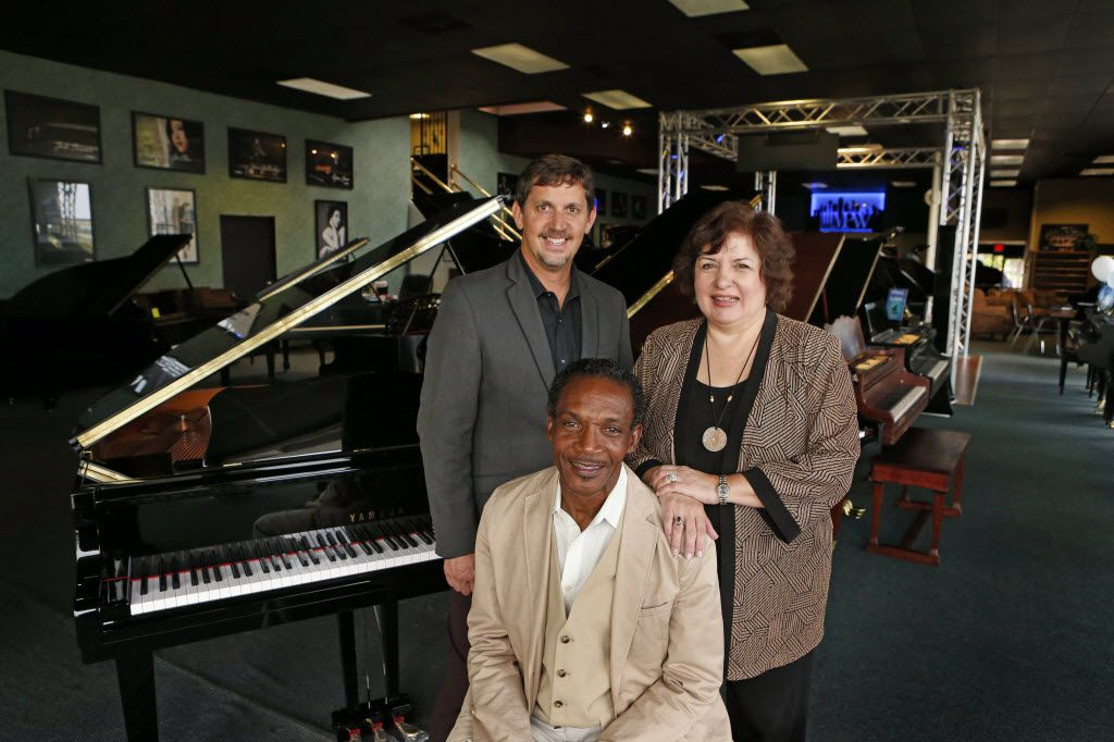 Johnnie Lindsey (seated), at Metroplex Piano with owner Darren Speir and Debbie Beach, photographed in June 2014. Lindsey donated keyboards to Beach so she could start a music school.