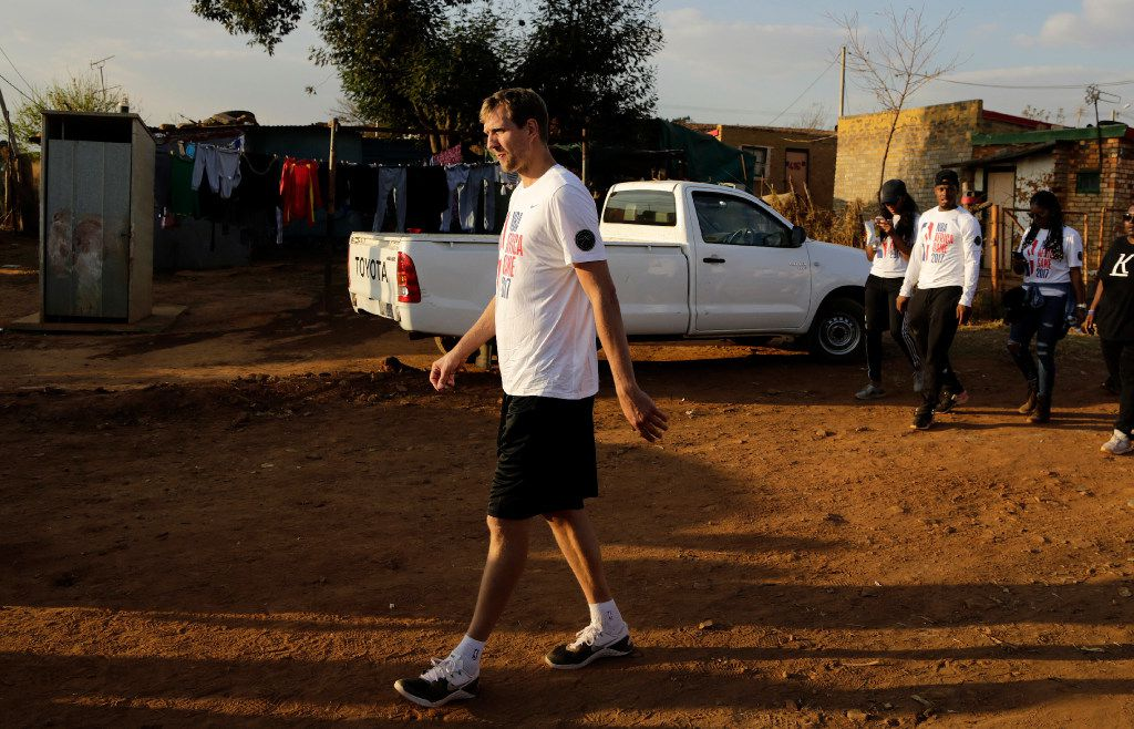 Dirk Nowitzki, of the Dallas Mavericks, walks on a dirt road after helping build a house in Lenasia South of Johannesburg, South Africa, Thursday, Aug. 3, 2017. As part of the NBA Africa Game, and Habitat for Humanity South Africa, 200 volunteers from the NBA players, families and executives help build 10 homes. (AP Photo/Themba Hadebe)