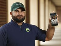 Marco Regalado holds up his phone where he posts Tik tok videos about football as he poses for a portrait at Northwest Eaton High School in Haslet, Texas on Monday, July 6, 2020. Regalado drew the attention of Northwest Eaton head coach Ellis Miller, who then hired him to be an assistant football coach in DFW.