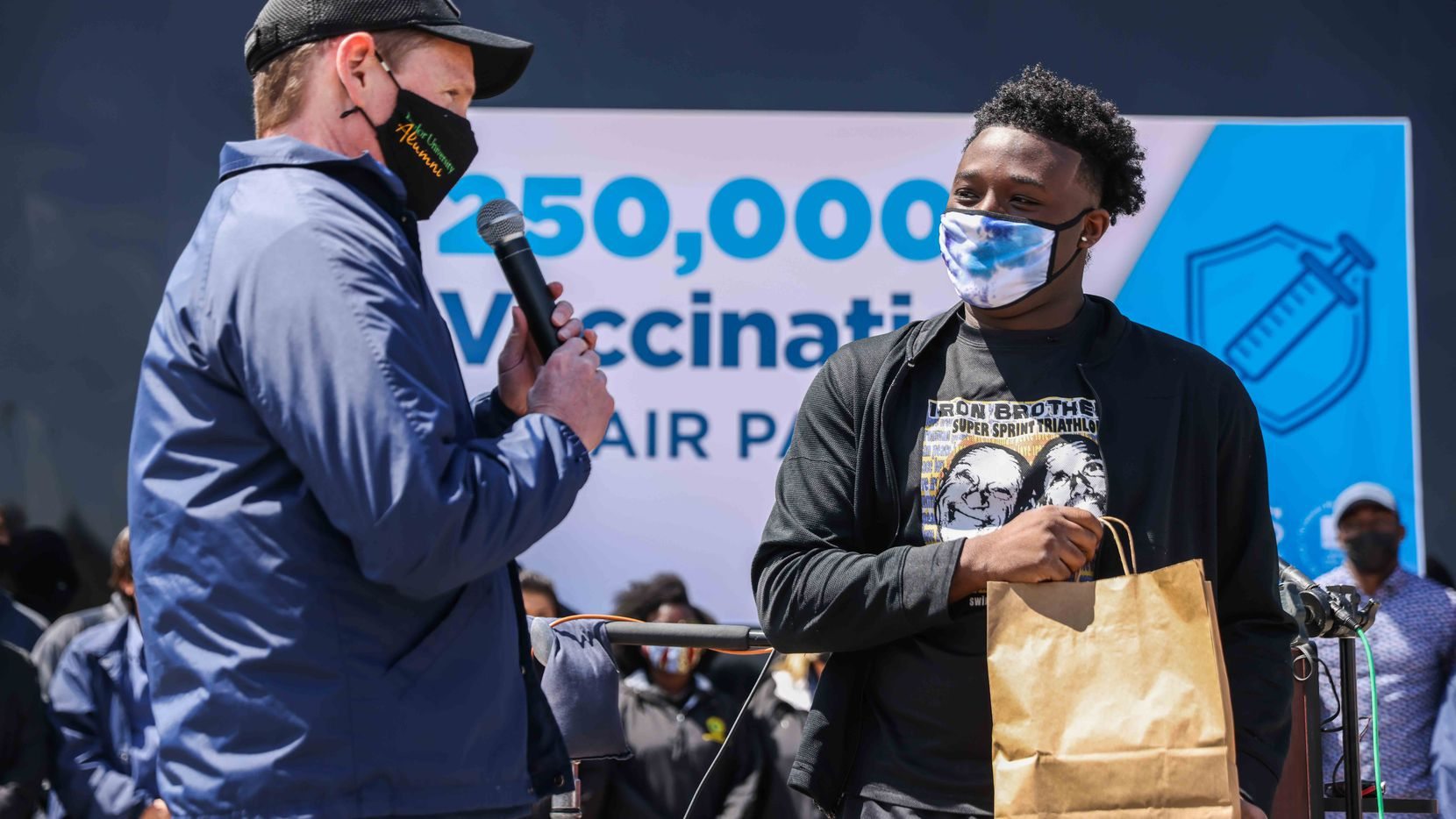 Dallas County Judge Clay Jenkins gave Quincy Williams, 20, who received the 250,000th vaccine provided by Dallas County, a certificate of the vaccination at Fair Park on March 31, 2021.