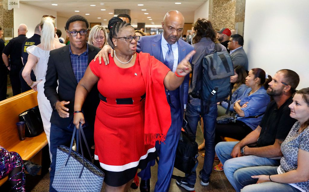 "Botham Jean's mother, Allison Jean (center), leaves the 204th District Court after fired Dallas police Officer Amber Guyger was found guilty of murder by a 12-person jury Oct. 1, 2019. She repeatedly said, ""God is good. Trust him,"" as she left the courtroom.  She was escorted by attorney Daryl Washington (right) and her son, Brandt Jean (left)."