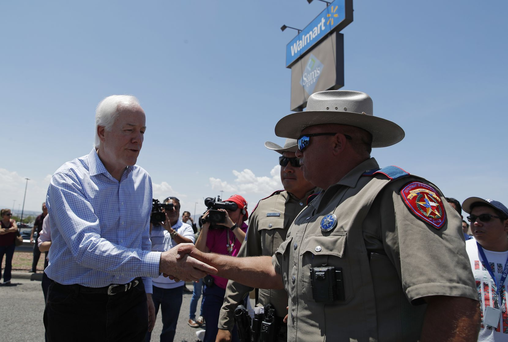 Sen. John Cornyn, R-Texas., left, shakes hands with law enforcement at the scene of a mass shooting at a shopping complex Sunday, Aug. 4, 2019, in El Paso, Texas.