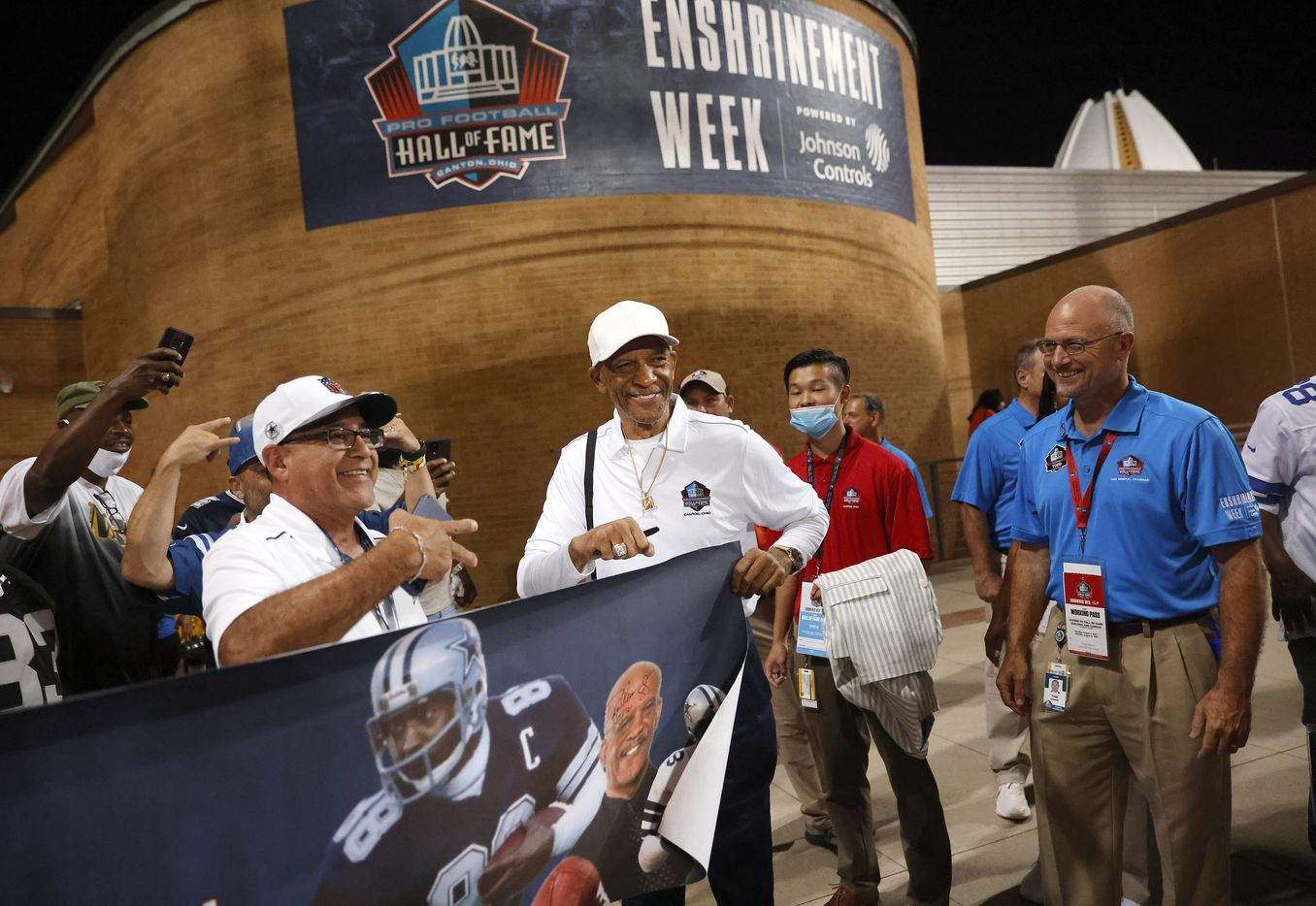 Pro Football Hall of Fame inductee Drew Pearson of the Dallas Cowboys (center) poses for photos with fans after signing a picture during a preseason game between the Cowboys and Pittsburgh Steelers at Tom Benson Hall of Fame Stadium in Canton, Ohio, Thursday, August 5, 2021. (Tom Fox/The Dallas Morning News)