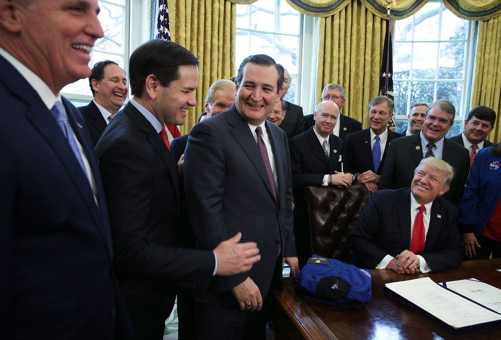 WASHINGTON, DC - MARCH 21:  U.S. Sen Marco Rubio (R-FL) (L) and Sen. Ted Cruz (R-TX) (R) share a moment as President Donald Trump looks on during a bill signing ceremony in the Oval Office of the White House March 21, 2017 in Washington, DC. President Trump has signed S.442 - National Aeronautics and Space Administration Transition Authorization Act of 2017 into law.  (Photo by Alex Wong/Getty Images)
