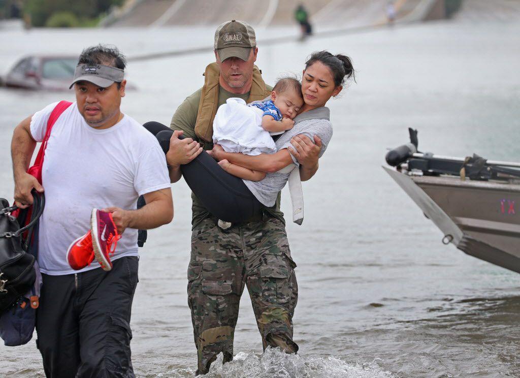 El oficial del Houston SWAT Daryl Hudeck carga a Catherine Pham y su hijo de 13 meses Aiden después de ser rescatadod via un bote en las inundaciones de la Interstatal 610 South en Houston./ (Louis DeLuca/The Dallas Morning News)